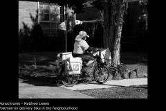 Postman on delivery bike in the neighbourhood - Matthew Leane